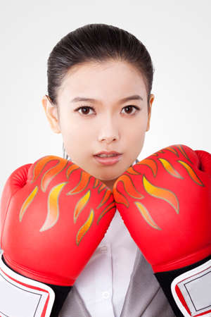 Business woman wearing boxing gloves
