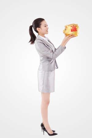 Oriental business woman and piggy bank Foto de archivo