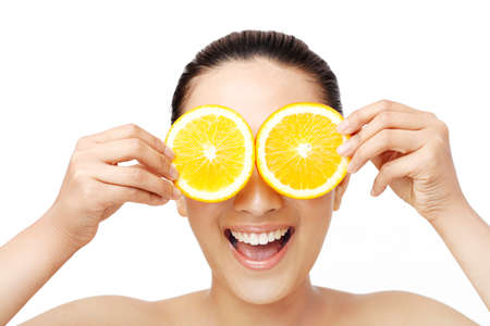 Oriental beauty with two slices of orange to cover the eyes Archivio Fotografico