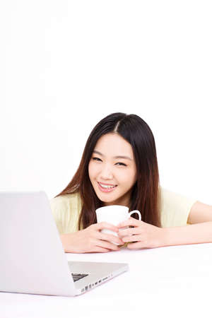 Young woman using laptop and holding a cup Stock Photo