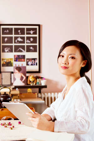 Oriental tea and young woman using tablet Stock fotó