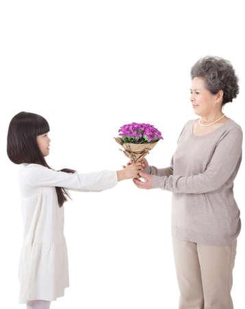 The little girl giving the grandmother flowers Foto de archivo