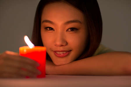 Young woman holding a red candle