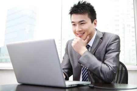 Businessman using laptop in office Фото со стока