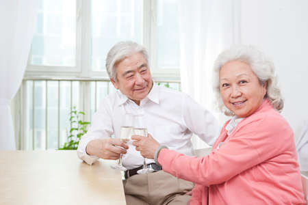 An old senior couple toasting for anniversary high quality photo