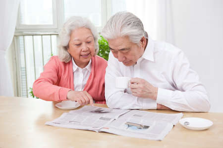 The happy old couple are reading the newspaper high quality photo