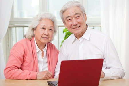 The happy old couple are using laptops high quality photo
