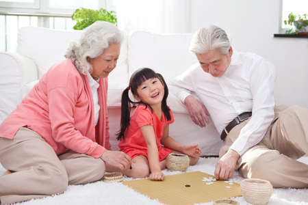 Senior couple with granddaughter playing game of go high quality photo