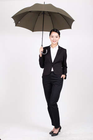 A young business woman holding an umbrella high quality photo