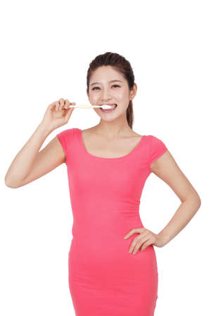 Young woman in pink dress holding toothbrush high quality photo