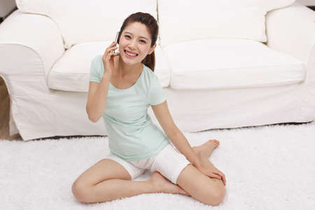 Young woman using cell phone beside a couch high quality photo
