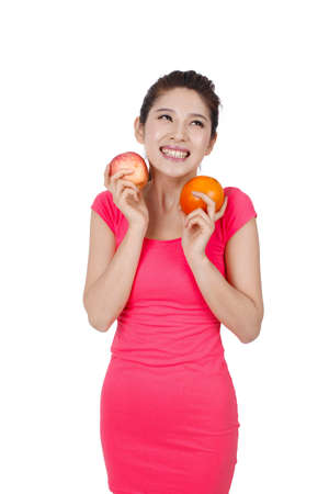 Young woman in pink dress holding apple and orange high quality photo
