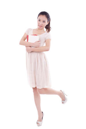 A Young woman standing, hugging a book high quality photo
