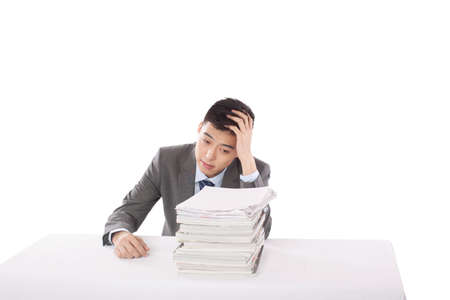 Portrait of young man sitting on desk with stack of files,portrait high quality photo