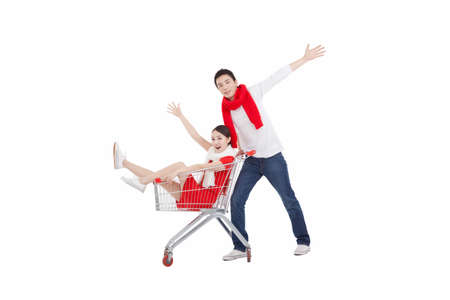 Portrait of wife sitting in shopping cart,husband pushing shopping cart,holding arms