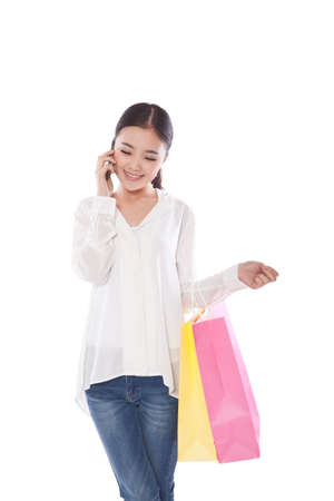 Young woman carrying shopping bags and calling high quality photo