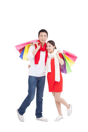 Portrait of young couple holding shopping bags over shoulders high quality photo