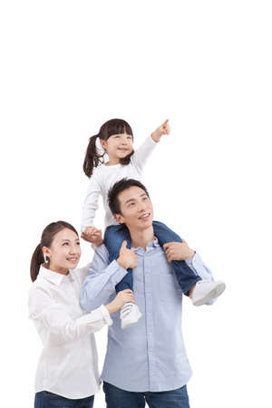 Portrait of daughter pointing,riding father s neck,with mother aside, looking up Stok Fotoğraf
