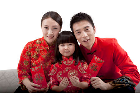Portrait of daughter with parents holding red envelopes,in Tang suits high quality photo