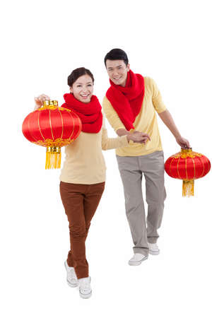 Portrait of young couple holding red lanterns