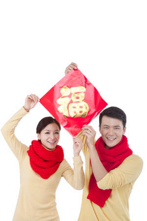 Portrait of young couple holding a Chinese Good Luck Fu,paying New Year call