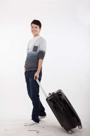 Portrait of young bisiness man pulling valise high quality photo