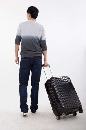 Portrait of young business man pulling valise high quality photo