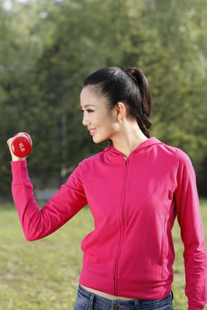 The young woman doing exercise with dumbbell in the outdoors high quality photo