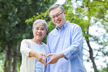 Portrait of happy old couple with Heart gesture