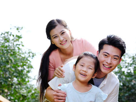 Happy family of three in the outdoor smiling Standard-Bild