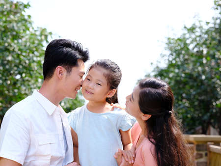 Father kissing on the cheek of the little girl with mother outdoors 版權商用圖片