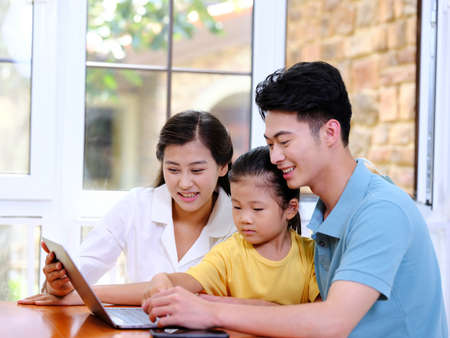 Happy family of three using laptop in the house 版權商用圖片