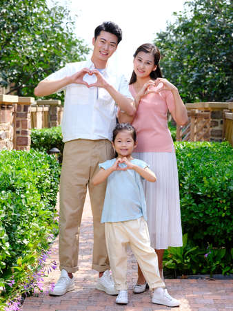 Happy family of three in the outdoor with heart gesture