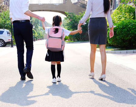 Young parents send their girl to school rear view
