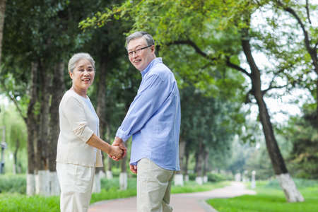 Happy old couple walking in the park hand in hand 版權商用圖片
