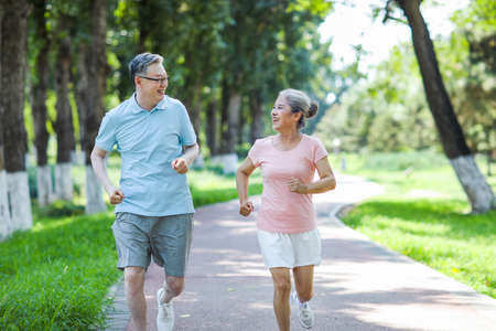 Old couple jogging in outdoor park smiling