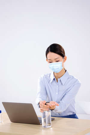 A business woman wearing a mask uses hand sanitizer side view