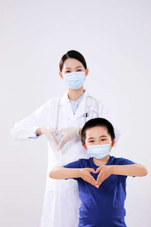 A woman doctor and a little boy made heart to heart gestures looking at the camera