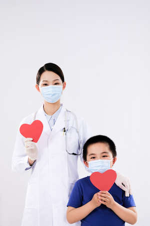 A woman doctor and a little boy each had a red heart lookingat the camera