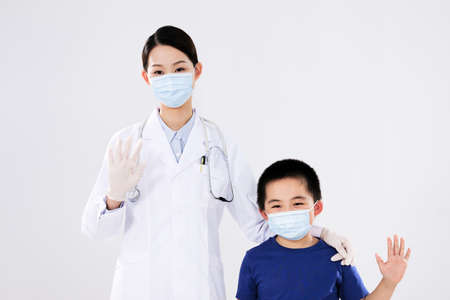 A woman doctor and a little boy waved smiling 版權商用圖片