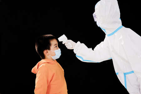 The woman doctor in medical protective clothing took the boys temperature face to face