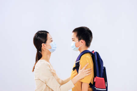 Mother puts on a mask for the boy who is going to school face to face