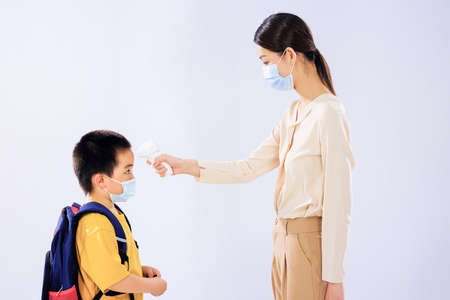The little boy took his temperature before school by his mom 版權商用圖片