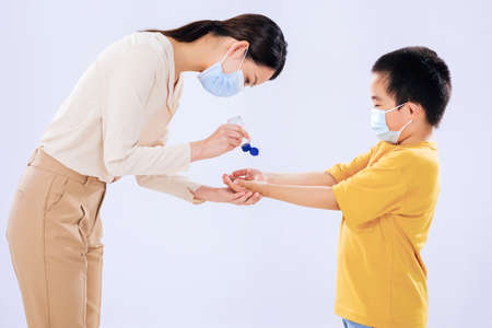 The mother taught the little boy to use hand sanitizer with his mom 版權商用圖片