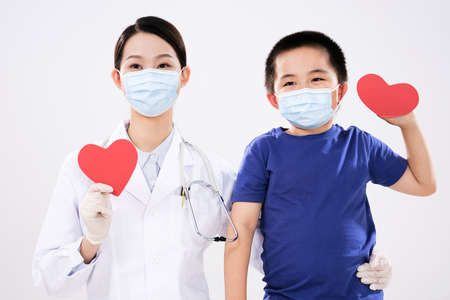 A woman doctor and a little boy each had a red heart looking at the camera 版權商用圖片