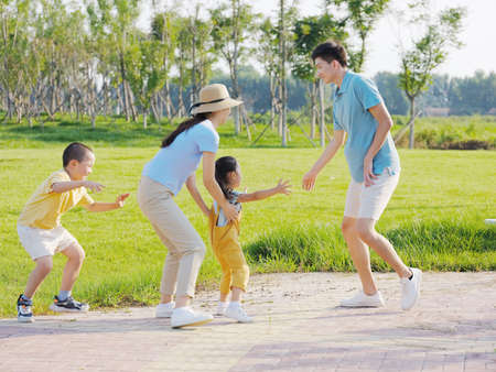 Happy family of four playing games in the park high quality photo Banque d'images