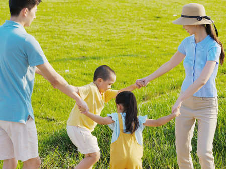 Happy family of four playing in the park high quality photo