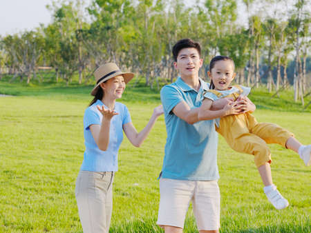 Happy family of three playing in the park high quality photo