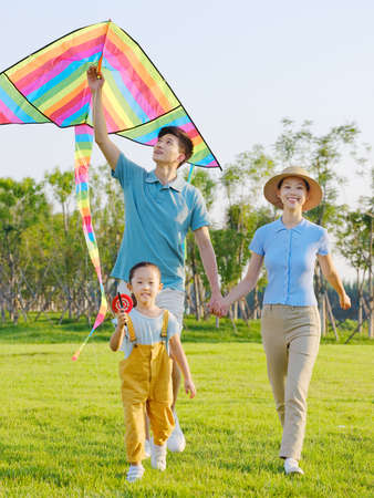 Happy family of three flying kites in the park high quality photo