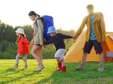 Happy family of four outdoor hiking high quality photo